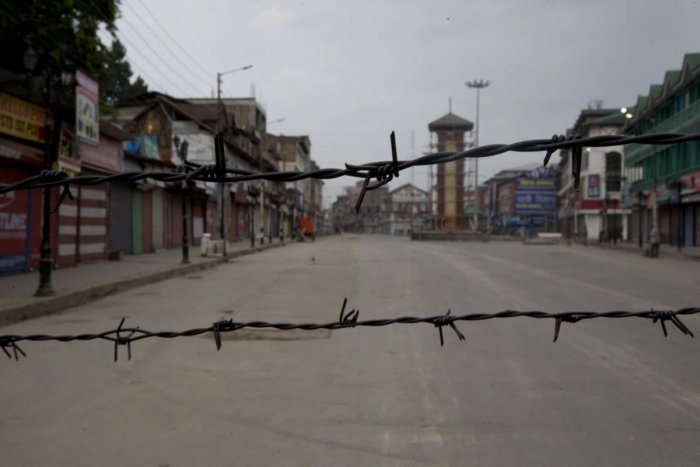 In this Tuesday, Aug 6, 2019 photo, a deserted street is seen through a barbwire set up as blockade during curfew in Srinagar. (AP/PTI Photo)