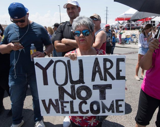 Anti-Trump protesters hold signs outside the makeshift memorial to the victims of the WalMart shooting that left a total of 22 people dead, in El Paso, Texas, on August 7, 2019. (AFP)