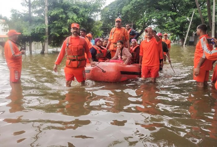 NDRF personnel rescue people stranded in flood waters on inflatable boats after heavy rains on the outskirts of Sangli in Maharashtra state. AFP photo