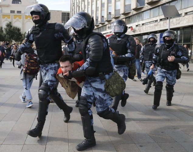 Police officers detain a protestor, during an unsanctioned rally in the center of Moscow. PTI Photo
