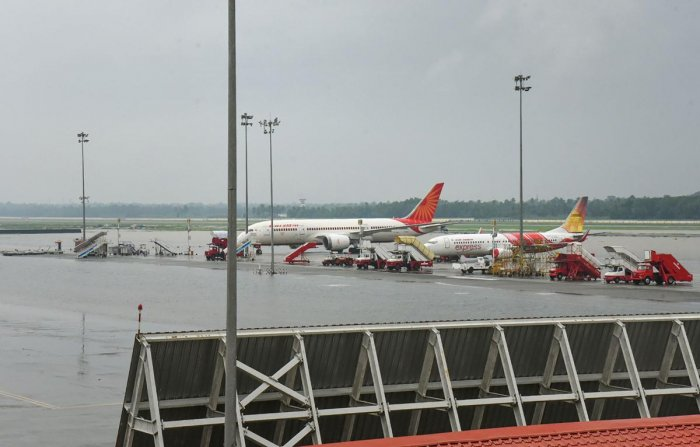 Planes stand parked at Cochin International Airport as all operations were suspended following waterlogging in the runway area. PTI Photo