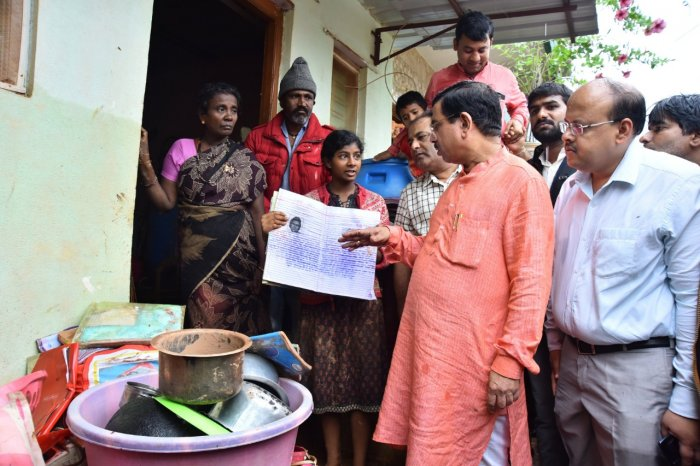 Pralhad Joshi interacts with a student whose books were damaged due to heavy rains in Hubballi. He assured of providing free books to all the students who lost their books in rain related incidents. DH photo