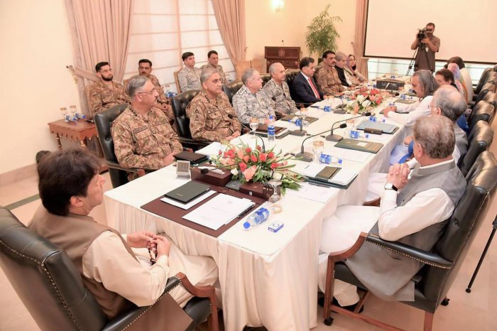 Pakistan Prime Minister Imran Khan (L) chairs the National Security Committee meeting in Islamabad. - Fears of an impending curfew in the disputed region of Kashmir ratcheted up tensions. (AFP Photo)