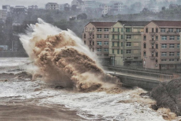 Waves hit a sea wall in front of buildings in Taizhou, China's eastern Zhejiang province. (AFP Photo)