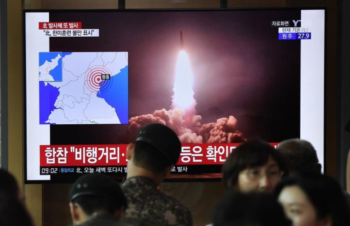 People watch a television news screen showing file footage of North Korea's missile launch, at a railway station in Seoul. (AFP Photo)