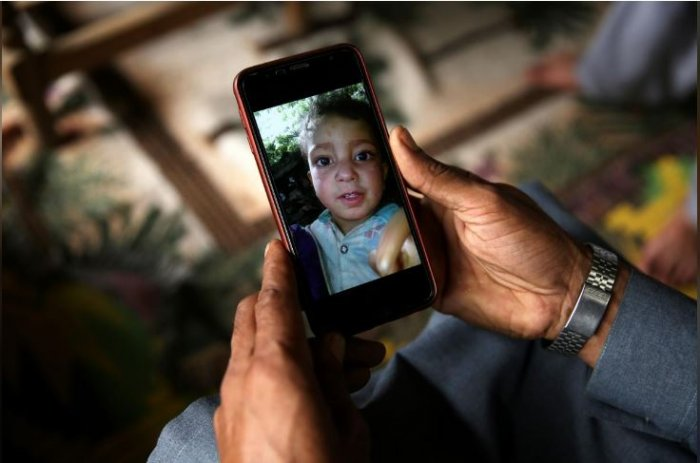 A relative displays the picture of 4-year-old Mohammad Ayan Ali, who, according to his family, was killed after he found a device that looked like a toy and exploded in his hands at home in the village of Jabri, in Neelum Valley, in Pakistan-administrated Kashmir. Pakistan's military says the device was an unexploded cluster bomb.. Picture taken August 9, 2019. REUTERS/Saiyna Bashir