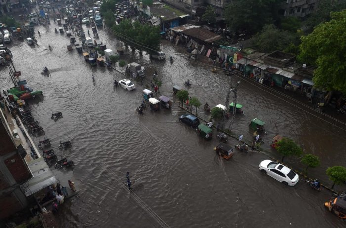 Commuters make their way on a flooded street after heavy monsoon rains in Lahore on August 1, 2019. (Photo by ARIF ALI / AFP)