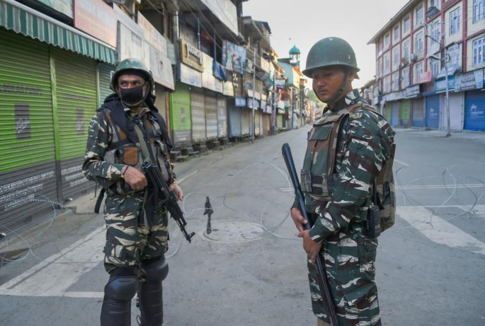 Security personnel stand guard during restriction in Srinagar. (PTI Photo)