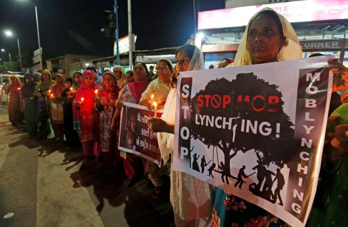 Women hold placards and candles during a protest against recent mob lynchings across the country, in Ahmedabad. REUTERS/ File photo