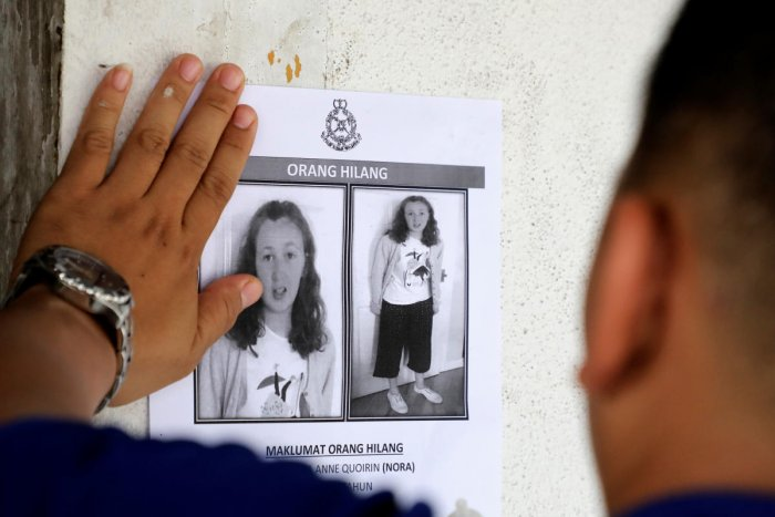 A police officer paste a photo of 15-year-old Irish girl Nora Anne Quoirin who went missing from a resort on a wall at a shop in Seremban, Malaysia. (Reuters Photo)
