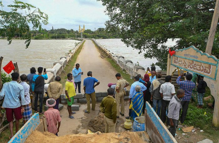 Visitors stand near the Wellesley Bridge over flooded Cauvery river, in Mandya, Sunday, Aug 11, 2019. PTI