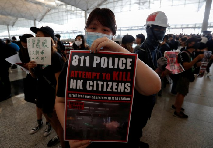 An anti-extradition bill demonstrator holds a placard during a protest at the departure hall of Hong Kong Airport, China. Reuters Photo