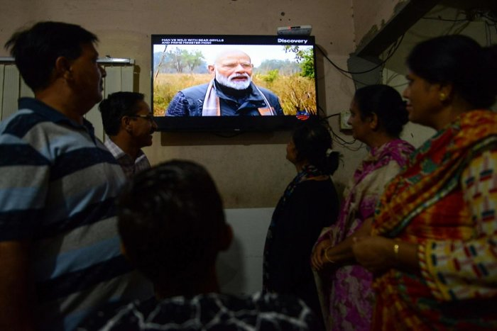 People watch on television the 'Man VS Wild' hosted by survival expert Bear Grylls, going on a mission with Indian Prime Minister Narendra Modi (C), in Amritsar on August 12, 2019. (AFP)