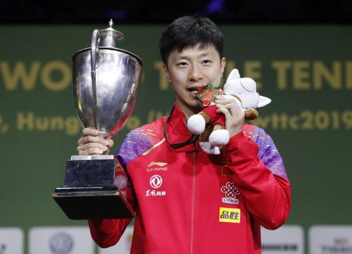 China's Ma Long with the trophy after winning the men's singles title at the World Table Tennis Championships in Budapest on Sunday. REUTERS