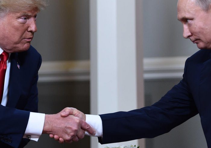 US President Donald Trump (L) and Russian President Vladimir Putin shake hands ahead of a meeting in Helsinki. (Photo by AFP)