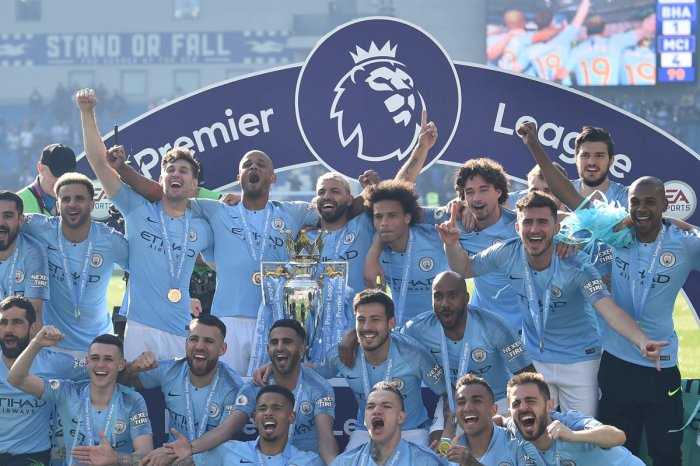 UNSTOPPABLE FORCE: Manchester City players celebrate with the Premier League trophy on Sunday. AFP