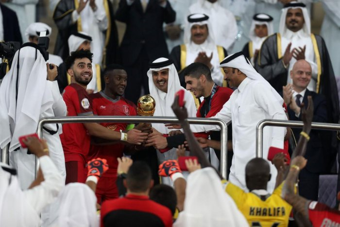 Qatar's Emir Tamim bin Hamad al-Thani (C) presents the trophy to the Duhail players following the Amir Cup final football match between Al Sadd and Al Duhail at the Al Wakrah Stadium in the Qatari city of Al Wakrah on May 16, 2019. - The 40,000-seater sta