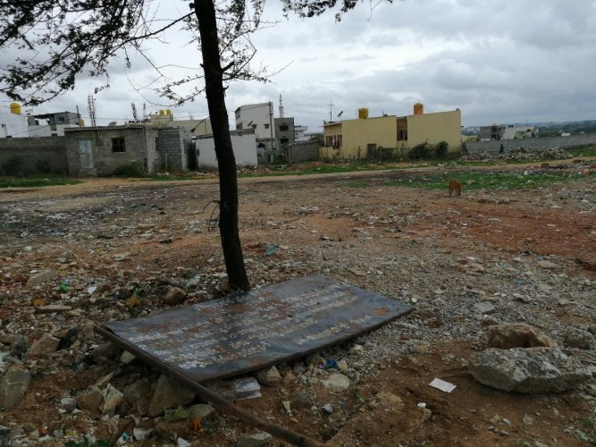 The 2-acres 35 gunta revenue land in Subash Nagar, Begur ward, which has been flattened by the unknown people alleged for the formation of the sites. The government board which has been removed is also seen lying in the land. DH Photo Sandesh MS