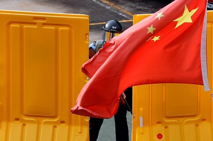 Chinese national flag flutters in front of a riot police officer during an anti-extradition bill protest at Sham Shui Po in Hong Kong, China August 11, 2019. REUTERS/Tyrone Siu