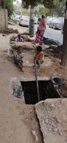 Sanitary workers clean gutters in Hoodi without protective equipment, as children are left unattended.