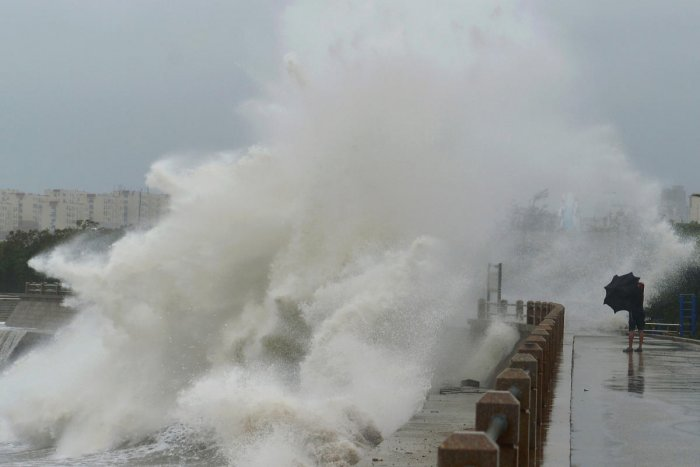 A wave brought by typhoon Lekima breaks on the shore next to a pedestrian in Qingdao, Shandong province. (Reuters file photo)