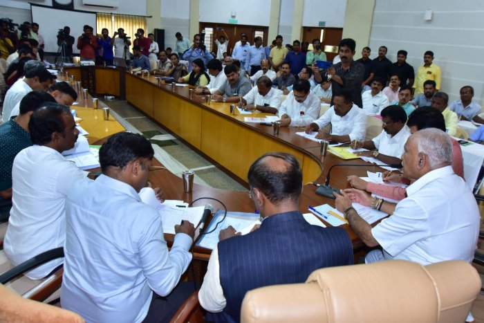 Chief Minister B S Yediyurappa chairs a review meeting after inspecting rain-hit areas, at Dharmasthala on Monday. DH Photo
