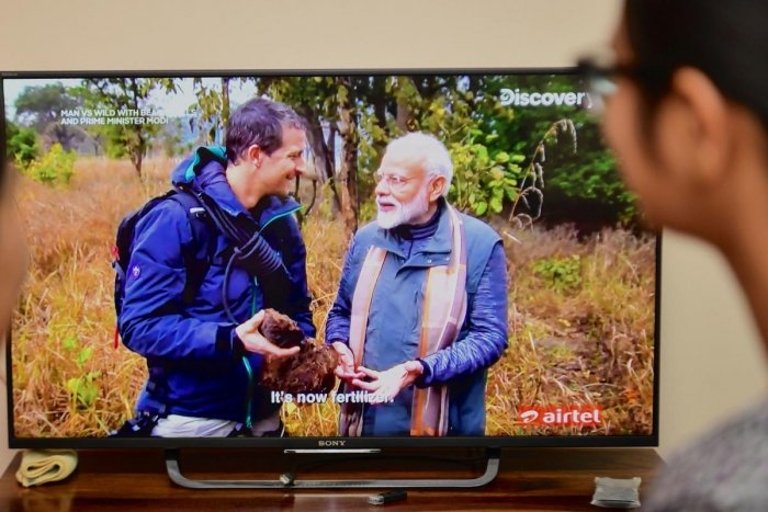 People watch on television the special edition of 'Man Vs Wild' series hosted by survival expert Bear Grylls (R), going on a mission with Indian Prime Minister Narendra Modi, in Bangalore on August 12, 2019. (AFP)