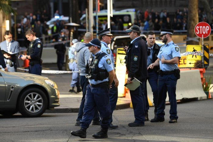 Police gather at the crime scene after a man stabbed a woman and attempted to stab others in central Sydney on August 13, 2019, before being pinned down by members of the public and detained by police. (AFP)