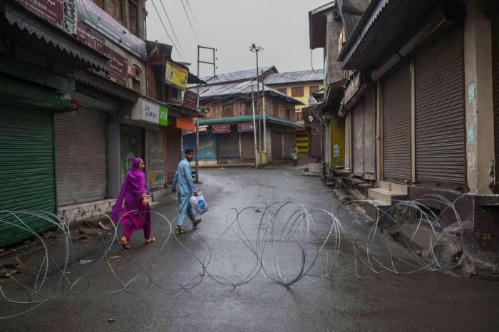A man and a woman walk in a street during curfew like restrictions following abrogation of the provisions of Article 370, in Srinagar. PTI photo