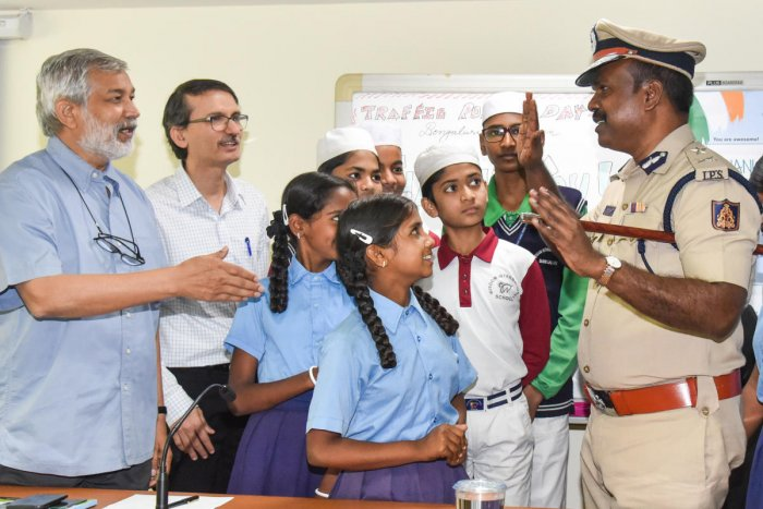 Harishekaran P, Additional Commissioner of Police (Traffic) interacting with students at Traffic Police Day programme organised by CMCA at Traffic Management Centre in Bengaluru on Monday, Ashish Patel, Director, CMCA, Ajai Kumar Singh, former DG and IGP