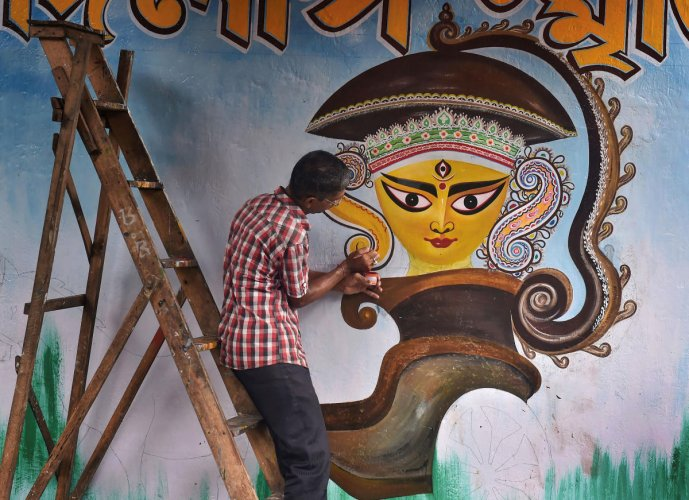An artist paints a graffiti of Hindu goddess Durga on a wall, part of a campaign ahead of upcoming Durga Puja festival, in Kolkata, on August 13, 2019. PTI