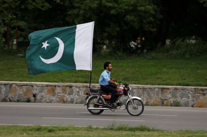 A man rides on a motorbike with a national flag ahead of country's Independence Day in Islamabad. Reuters photo
