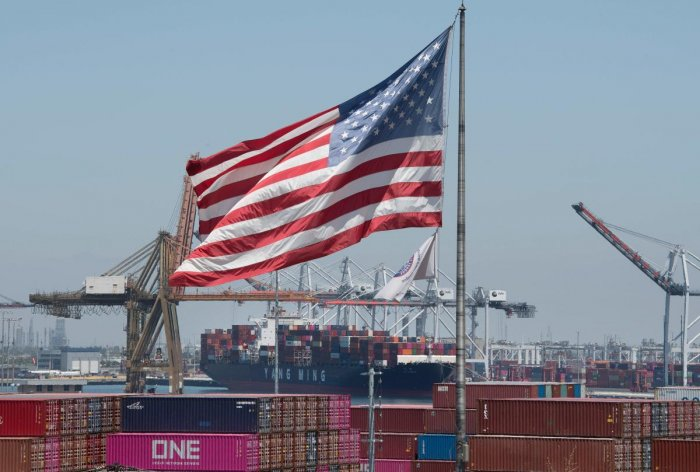 The US flag flies over a container ship unloading it's cargo from Asia, at the Port of Long Beach, California on August 1, 2019. - President Donald Trump announced August 1 that he will hit China with punitive tariffs on another $300 billion in goods, esc