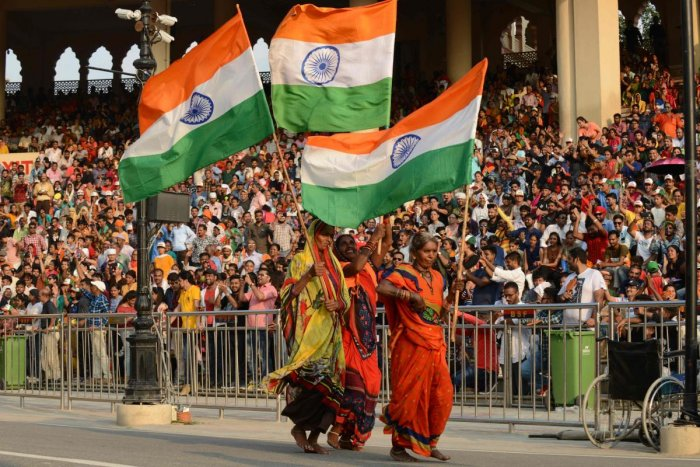 Indian women carry Indian flags during the Beating Retreat ceremony at the India Pakistan Wagah border post some 35 kms from Amritsar on August 10, 2019. (Photo by NARINDER NANU / AFP)