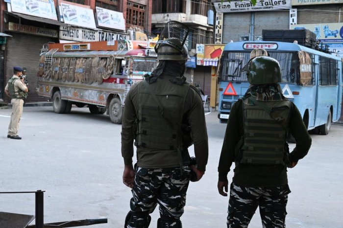 Security personnel stand guard on a street during a lockdown in Srinagar on August 12, 2019. - Indian troops clamped tight restrictions on mosques across Kashmir for Eid al-Adha festival, fearing anti-government protests over the stripping of the Muslim-m