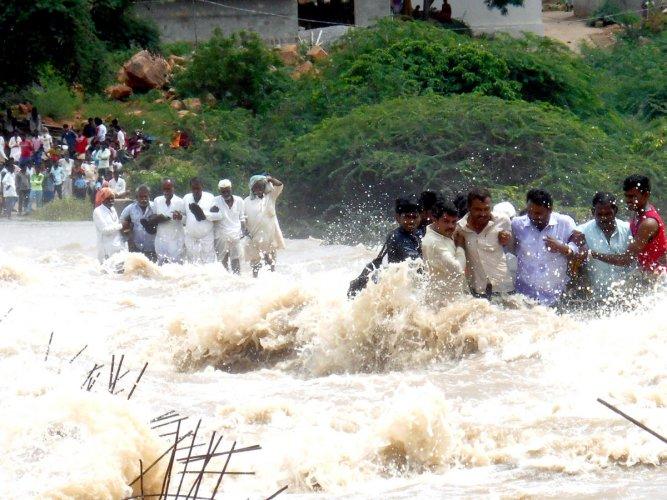 Villagers stranded at Jaladurg village in Lingasugur taluk of Raichur district cross the swollen Krishna river on inundated bridge on Thursday. DH PHOTO/B A NANDIKOLMATH