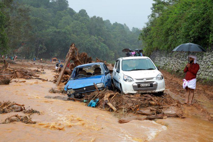 A man stands next to damaged cars after a landslide caused by torrential monsoon rains at Puthumala near Meppadi, Wayanad district, Kerala. Reuters photo