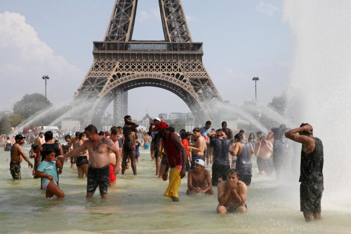 People cool off in the Trocadero fountains across from the Eiffel Tower in Paris as a new heat wave broke temperature records in France. (Reuters file photo)