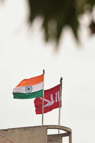 In this picture taken on August 6, 2019 an Indian national flag flies next to a Jammu and Kashmiri flag ontop of civil secretariat building during a curfew in Srinagar on August 6, 2019. AFP