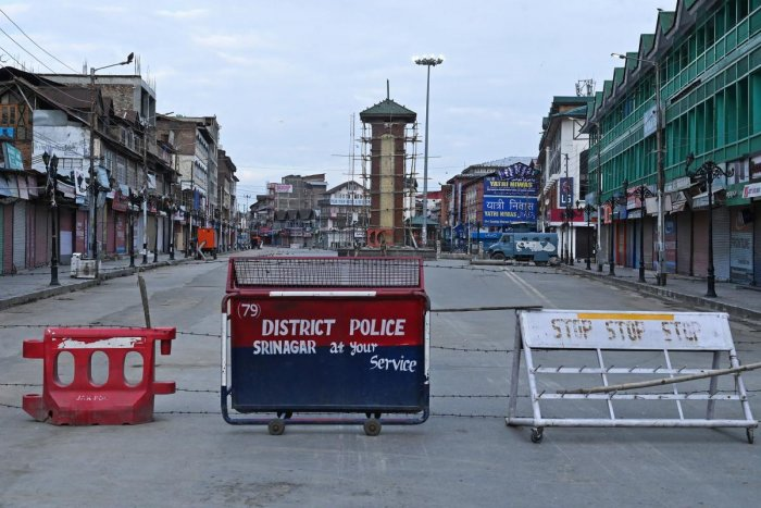 Security personnel (back) stand guard a street under the clock tower at Lalchowk during a lockdown in Srinagar. (AFP Photo)