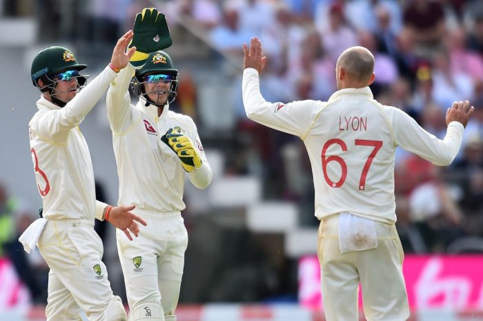 Australia's Nathan Lyon (R) and Australia's captain Tim Paine (C) celebrate the wicket of England's Stuart Broad for 11 runs on the second day of the second Ashes cricket Test match between England and Australia at Lord's Cricket Ground in London on Augus