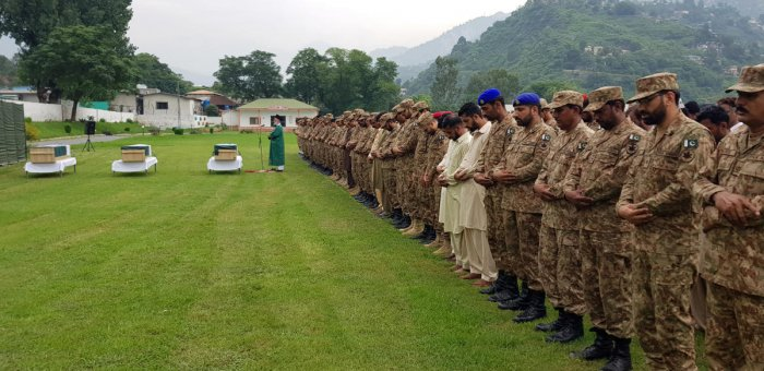 Army soldiers and civilians attend the funeral of three soldiers who, according to Pakistan Army, were killed in a cross-border exchange of fire on the Line of Control (LOC), at army stadium in Muzaffarabad, Pakistan-administrated Kashmir August 16, 2019.