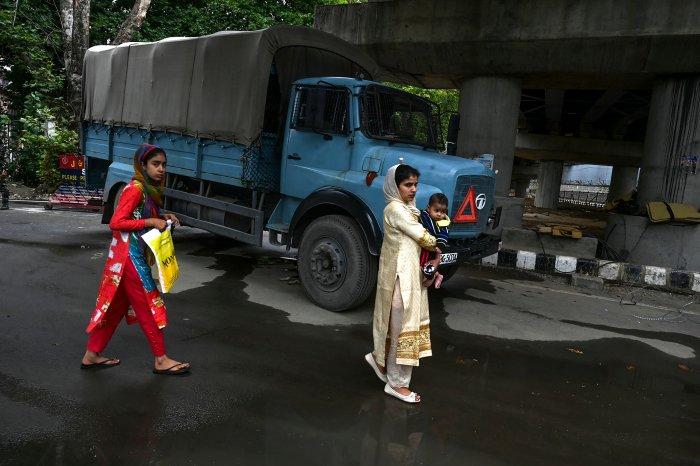 Kashmiri pedestrians walk past a security personnel vehicle in Srinagar. (AFP Photo)