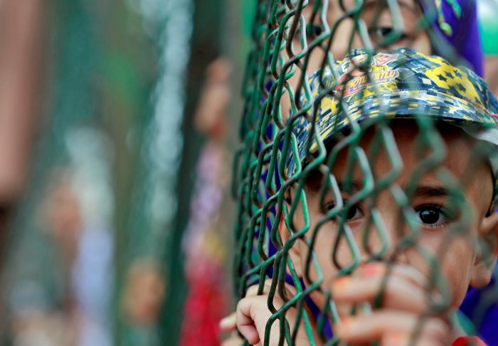 Kashmiri child looks from behind a fence at a protest site after Friday prayers during restrictions after the Indian government scrapped the special constitutional status for Kashmir, in Srinagar, August 16, 2019. REUTERS