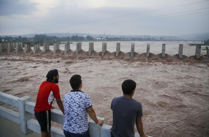 A group of people watch the swollen Tawi river following heavy rainfall, in Jammu, Wednesday, Aug 14, 2019. (PTI Photo for representation)