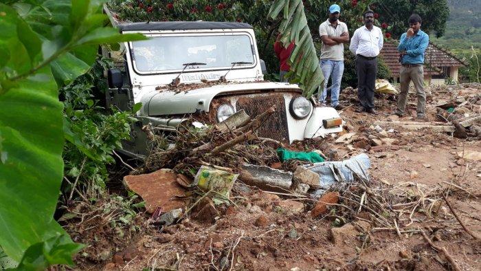 A jeep belonging to Natesh is half buried after a landslide at Hallikere in Kottigehara.