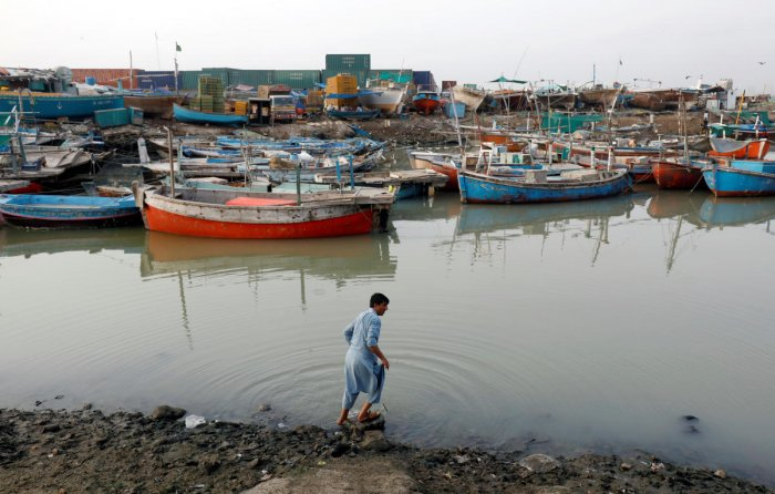 A man washes his feet in front of anchored fishing boats, near the port area in Karachi, Pakistan August 1, 2019. REUTERS/Akhtar Soomro