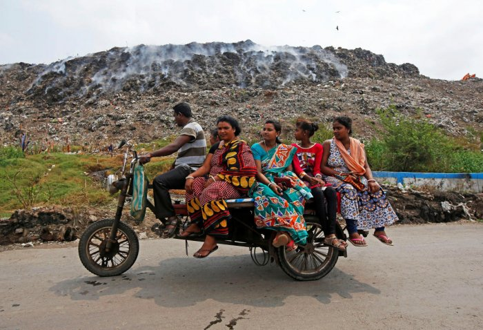 A man transports passengers on an improvised motor-rickshaw as they drive past a burning garbage dump site on the occasion of Earth Day, in Kolkata, India, April 22, 2018. REUTERS