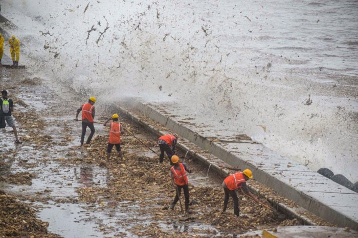 Brihanmumbai Municipal Corporation (BMC) workers clear the garbage washed ashore during high tide, on the promenade along the Marine Drive, in Mumbai, Saturday, Aug 3, 2019. (PTI Photo)