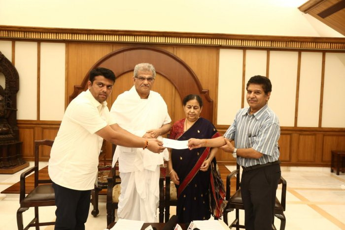 Belthangady MLA Harish Poonja receives cheque for Rs 50 lakh from SKDRDP Executive Director Dr L H Manjunath to take up relief works in the taluk. Dharmadhikari D Veerendra Heggade, and Hemavathi V Heggade looks on.